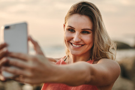Woman taking selfie standing at the beach