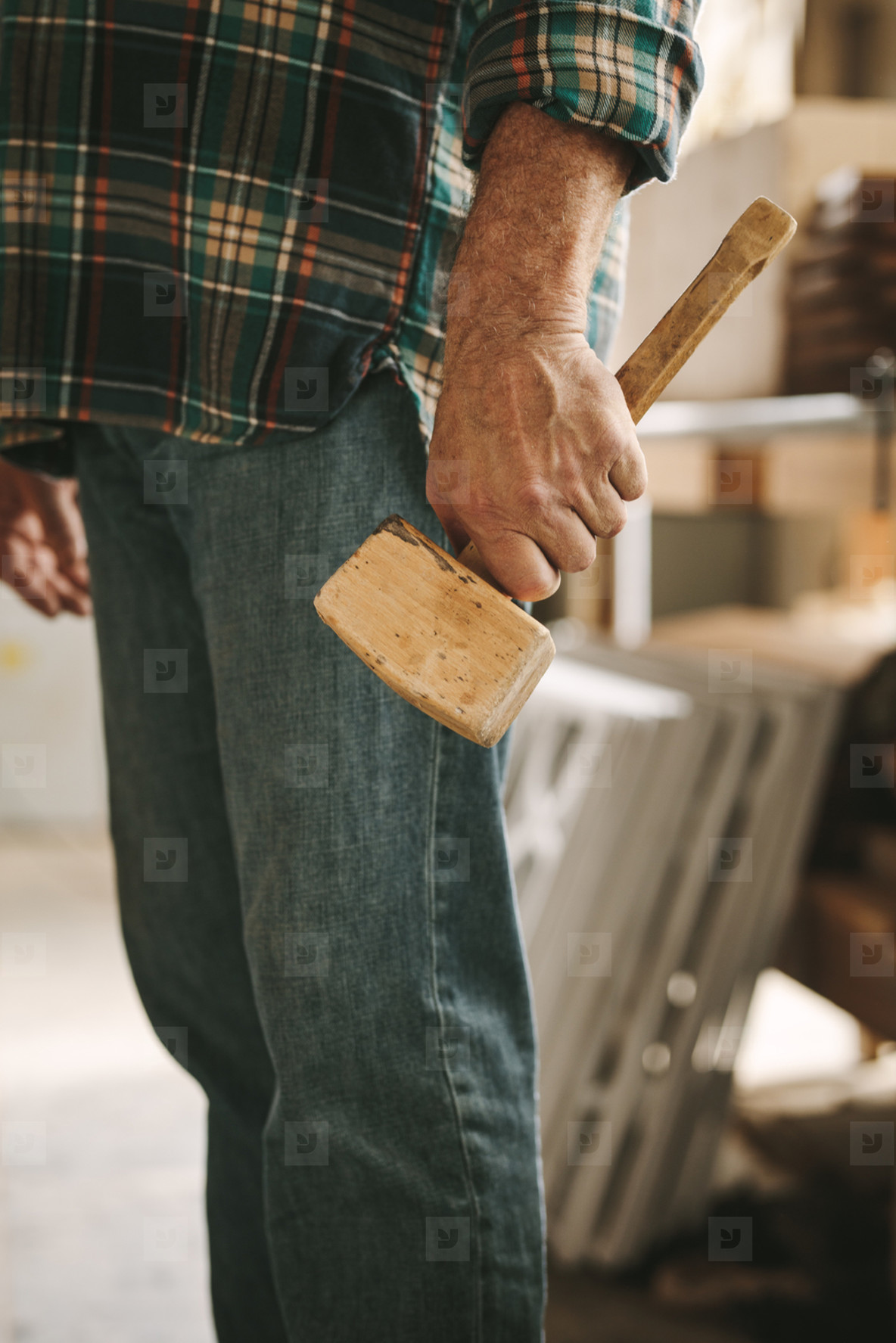 Carpenter with mallet hammer at workshop