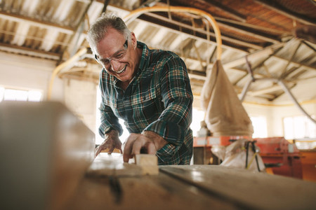 Smiling mature man working in carpentry workshop