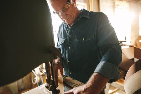 Senior male carpenter working on band saw machine