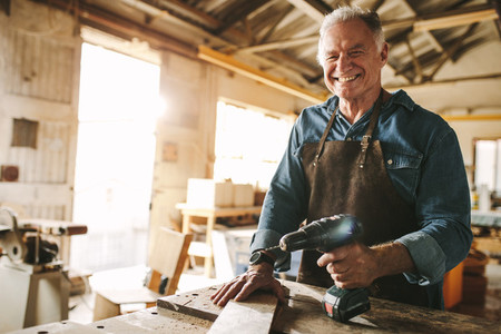 Senior male carpenter working at his workshop