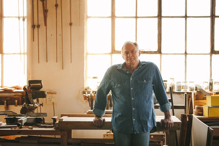 Senior man standing by a table in his carpentry workshop