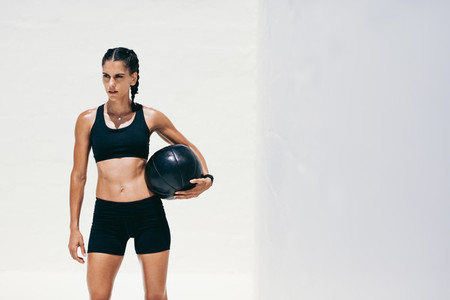 Portrait of a fitness woman standing holding a medicine ball