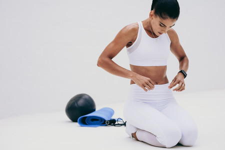Fitness woman sitting on floor with her fitness equipment
