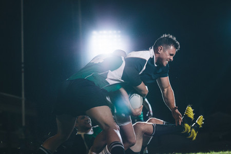 Rugby players blocking the opponent