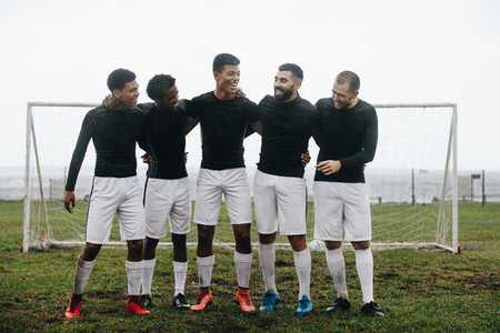 Group of soccer players standing near the goalpost