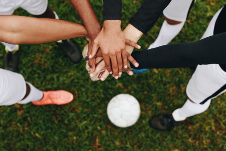 Close up of hands of players standing together in a huddle