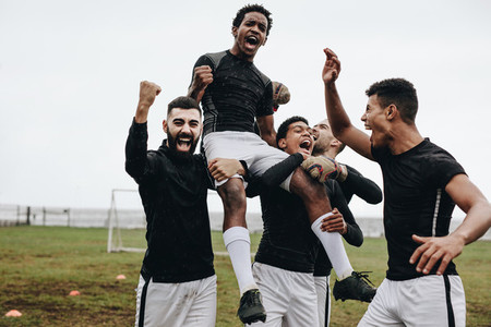 Soccer players celebrating success by lifting a teammate on shou