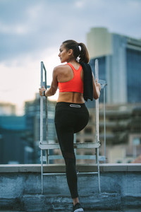 Female athlete standing on rooftop metal stairs