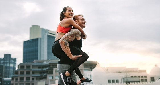 Cheerful man carrying a fitness woman on his back walking on roo