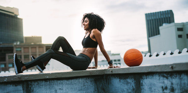Female athlete relaxing on the rooftop fence