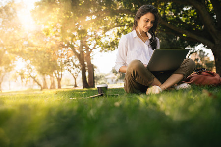 Woman sitting on grass at park working on laptop