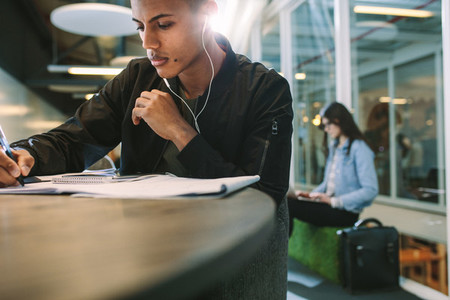 Student at the library listen to music and making notes