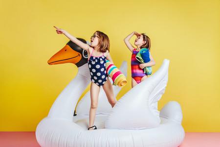 Twin sisters in swimwear on inflatable flamingo looking away
