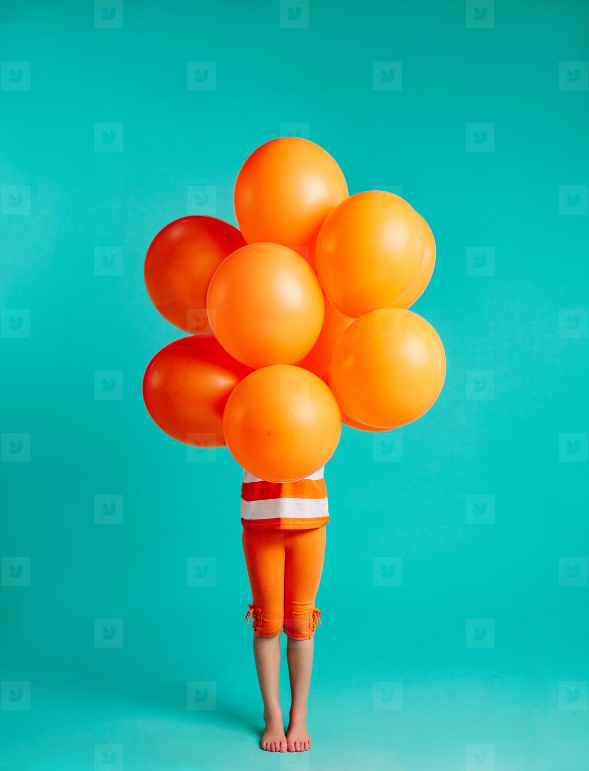 Girl holding orange balloons in front