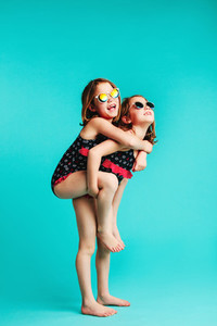 Girl in swimwear giving piggyback ride to her friend
