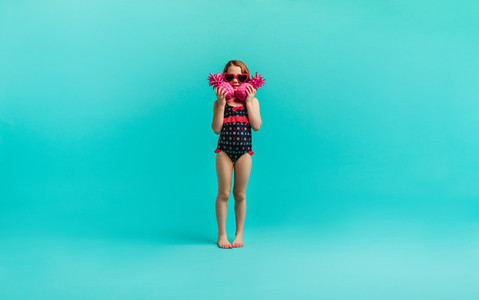 Girl in swimwear with two pink pineapples
