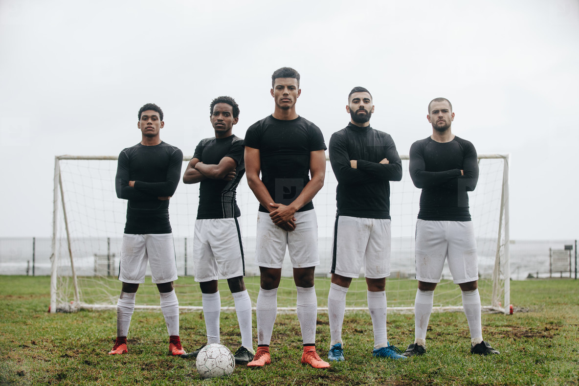 Football players standing on a soccer field in front of goalpost