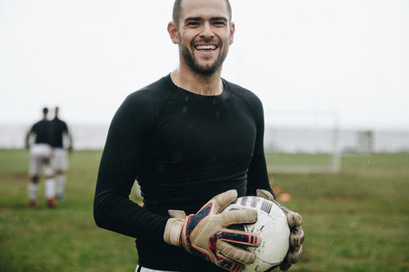 Close up of a smiling soccer player standing on field