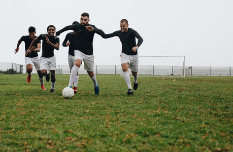 Group of men playing soccer on the field