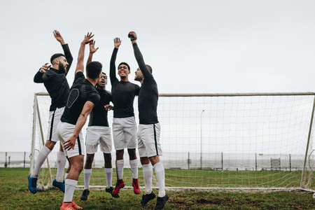Soccer players jumping in place after a pep talk