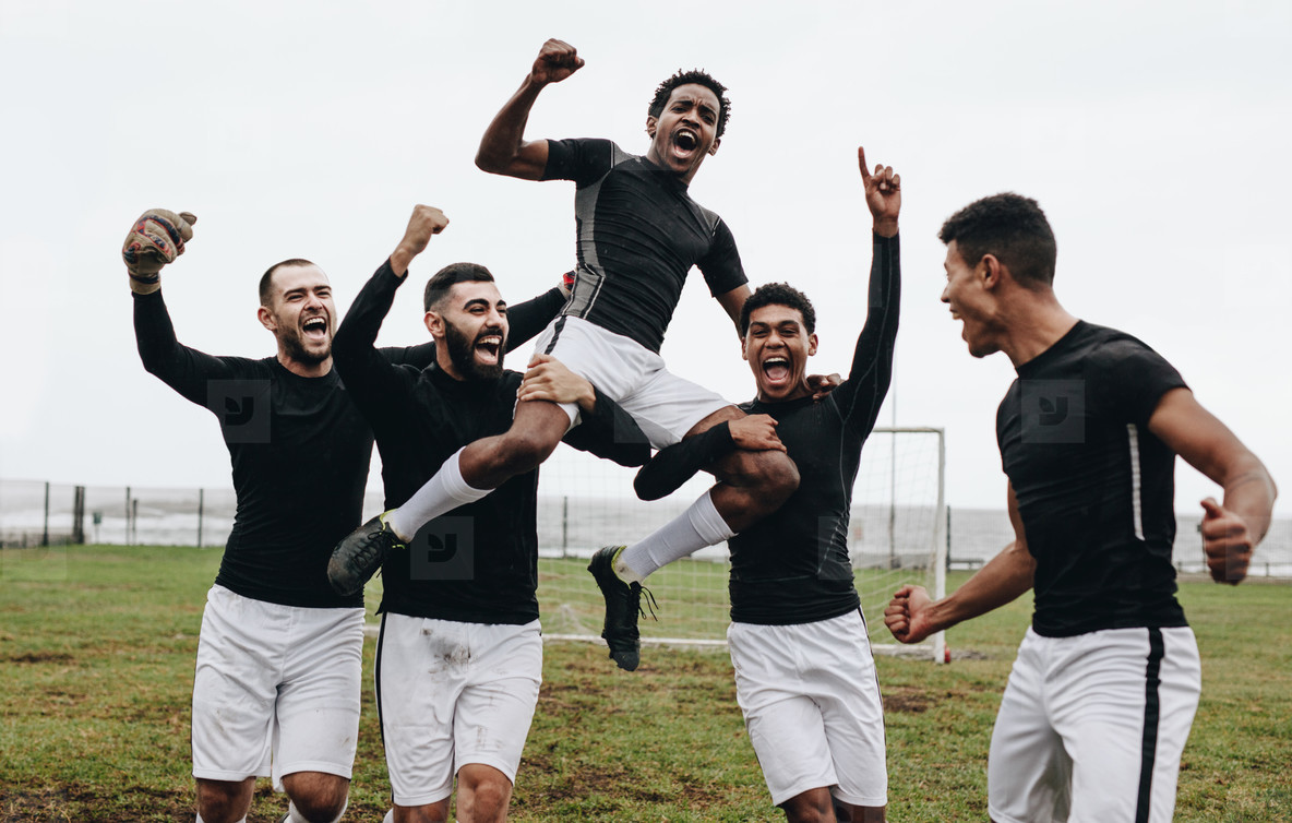 Footballers celebrating success on field