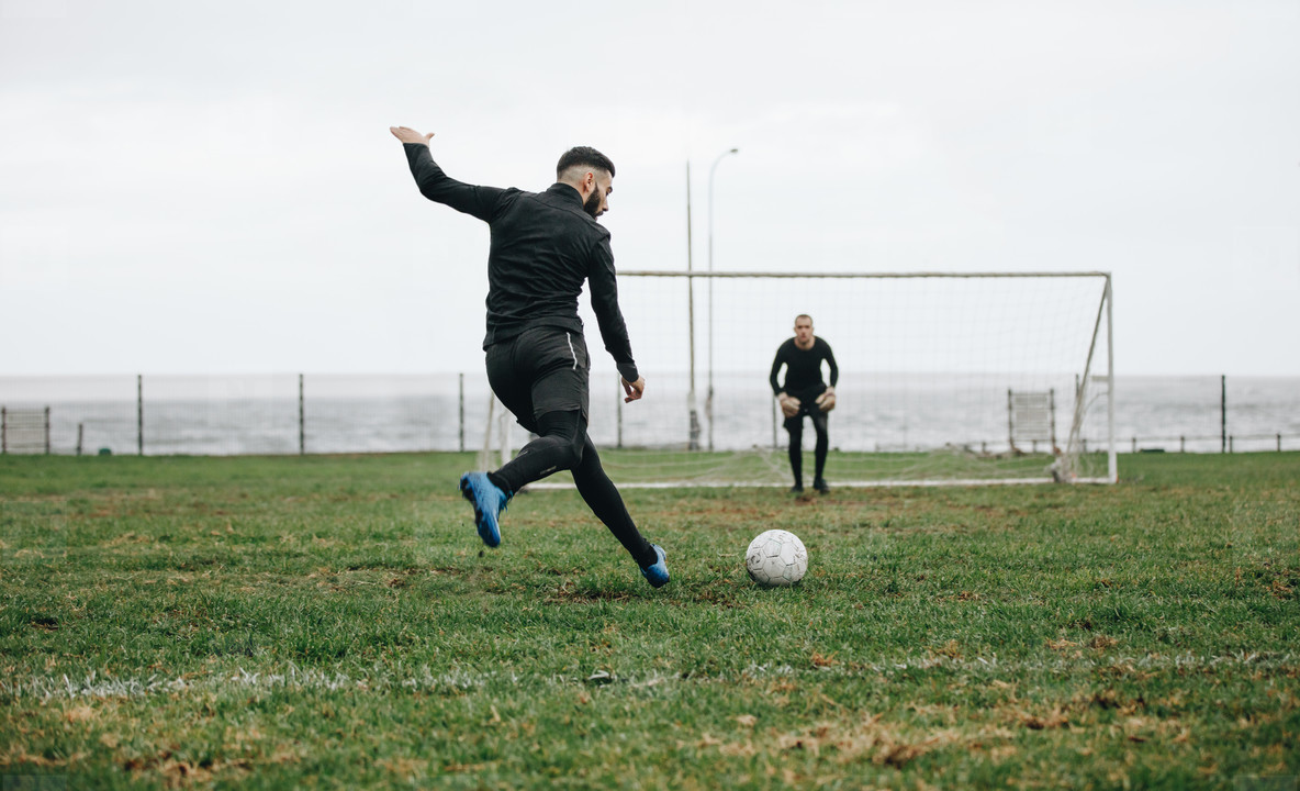 Men playing soccer on field near the sea