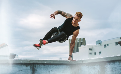 Athletic man doing fitness training on rooftop