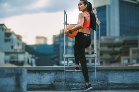 Female athlete standing on rooftop staircase looking away