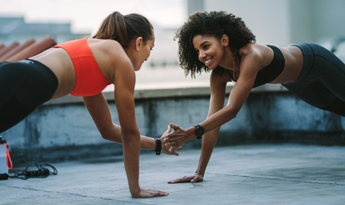 Two fitness women training together on rooftop
