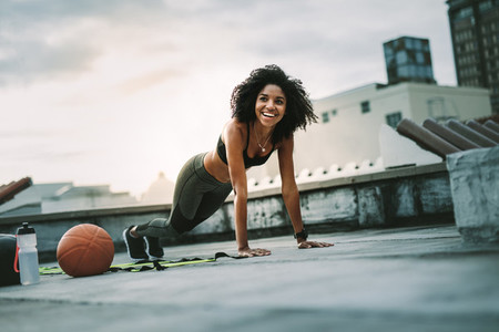 Fitness woman doing push ups on rooftop