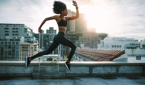 Fitness woman running on rooftop