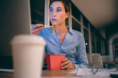 Businesswoman having food while working late in office