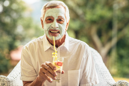 Fully elderly man with clay mask on face having juice