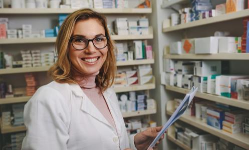 Positive female pharmacist working in pharmacy