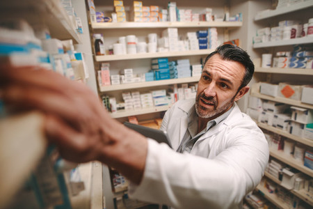 Pharmacy store owner checking stock on shelves