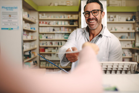 Apothecary taking prescription from customer