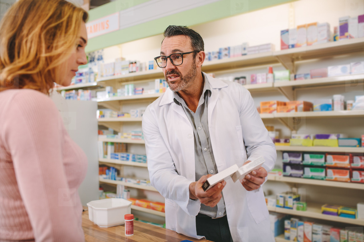 Pharmacist with a medicine box giving advice to customer