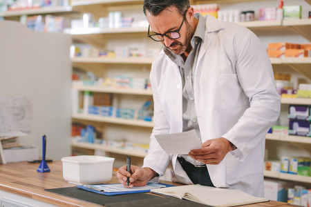 Pharmacist writing prescription pharmacy counter
