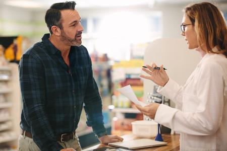 Pharmacist explaining a prescription to customer