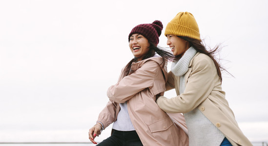 Two asian women in winter clothes standing together outdoors