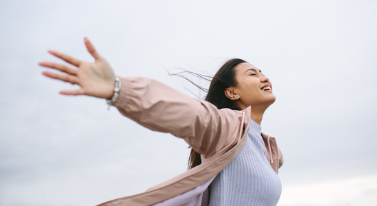 Asian woman enjoying nature standing with open arms