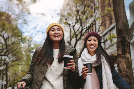 Asian women walking on street holding coffee