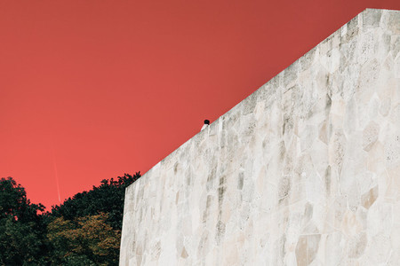 A man sitting on the edge of a stone wall