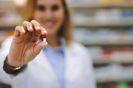 Female pharmacist holding a medicine capsule