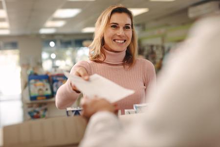 Customer giving a prescription to the chemist