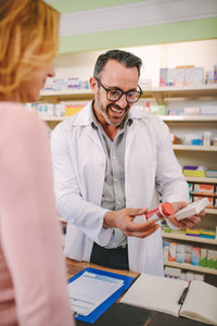 Chemist suggesting medical drug to buyer at pharmacy
