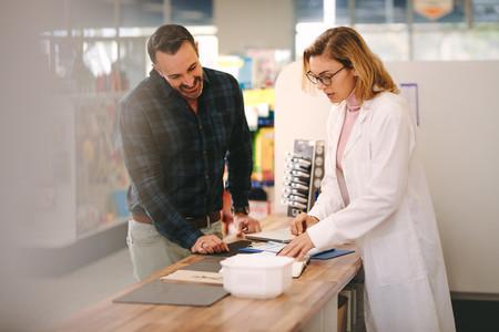 Chemist explains a prescription to customer