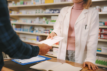 Customer handing over a prescription to the chemist