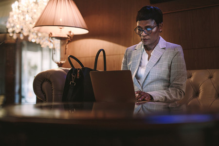 Female CEO on business trip using laptop in hotel lobby